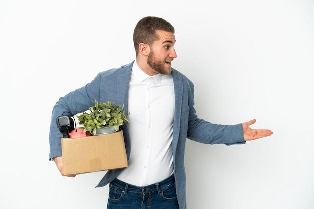 Jovem caucasiana se mexendo enquanto pega uma caixa cheia de coisas isoladas no fundo branco com expressão de surpresa enquanto olha para o lado