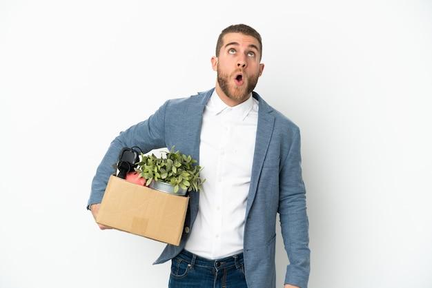 Jovem caucasiana se mexendo enquanto pega uma caixa cheia de coisas isoladas no fundo branco olhando para cima e com expressão de surpresa