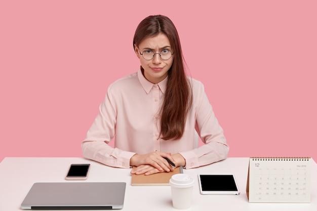 Jovem caucasiana séria usa óculos, camisa formal, tem tudo em ordem à mesa, rodeada de bugigangas modernas, bloco de notas para registros