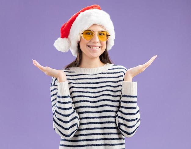 Jovem caucasiana sorridente com óculos de sol e chapéu de papai noel de mãos abertas