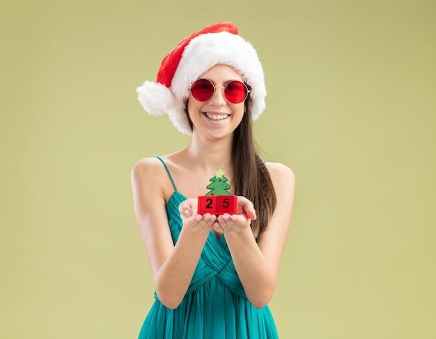 Jovem caucasiana sorridente com óculos de sol e chapéu de papai noel segurando enfeite de árvore de natal