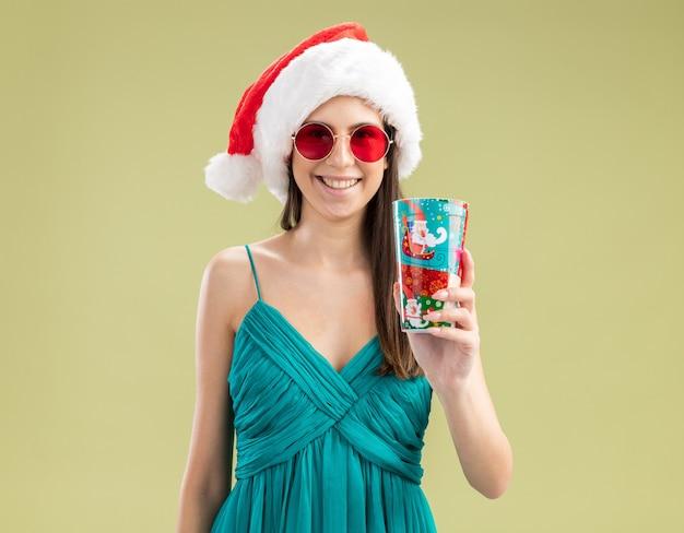 Jovem caucasiana sorridente com óculos de sol e chapéu de papai noel segurando um copo de papel