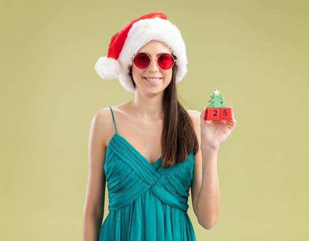 Jovem caucasiana sorridente com óculos de sol e chapéu de papai noel segurando um enfeite de árvore de natal