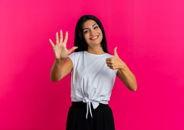 Jovem caucasiana sorridente gesticula seis com os dedos