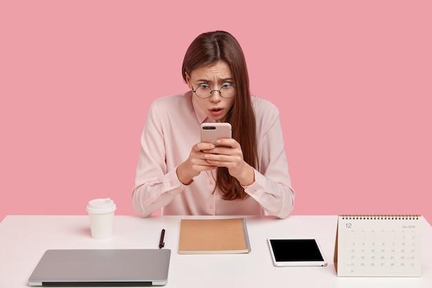 Jovem caucasiana surpresa com a respiração suspensa, usa novo smartphone para bate-papo e comunicação, mantém os olhos arregalados