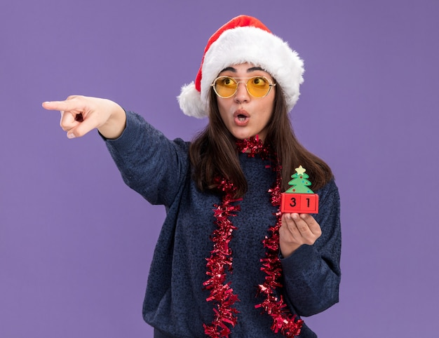 Jovem caucasiana surpresa com óculos de sol com chapéu de papai noel e guirlanda em volta do pescoço segurando enfeite de árvore de natal e aponta ao lado isolado na parede roxa com espaço de cópia