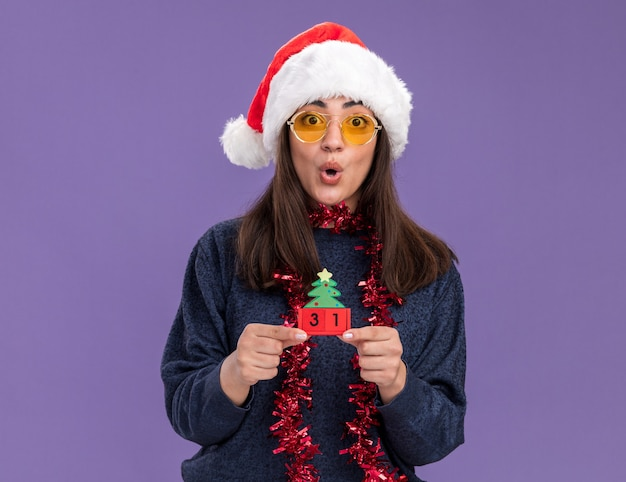 Jovem caucasiana surpresa com óculos de sol com chapéu de papai noel e guirlanda em volta do pescoço segurando um enfeite de árvore de natal isolado na parede roxa com espaço de cópia