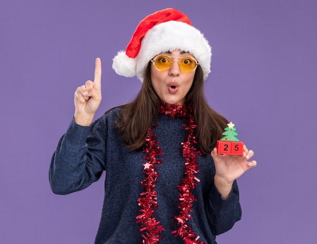Jovem caucasiana surpresa com óculos de sol com chapéu de papai noel e guirlanda no pescoço segurando enfeite de árvore de natal e aponta para cima isolada na parede roxa com espaço de cópia