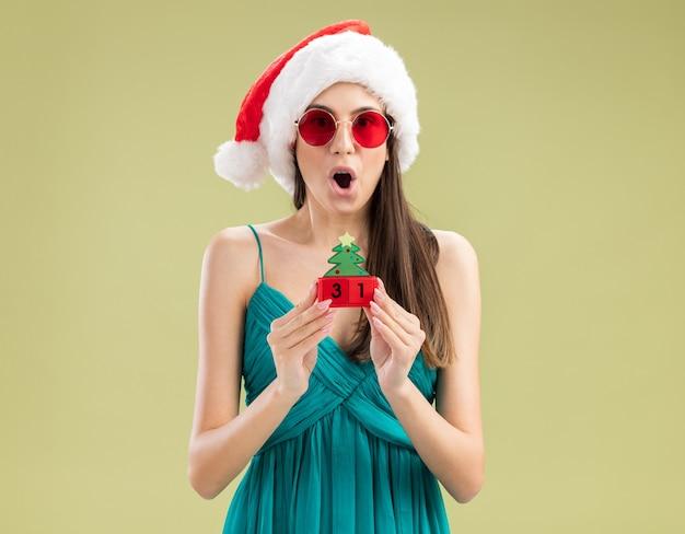 Jovem caucasiana surpresa com óculos de sol e chapéu de papai noel segurando enfeite de árvore de natal