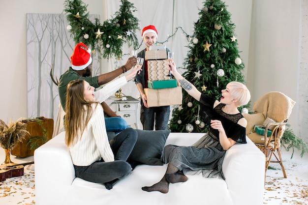 Jovem caucasiano apresentando presentes de natal para amigos no sofá na festa de ano novo