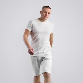 Jovem caucasiano atraente em uma camiseta em branco e shorts cinza de malha em um fundo branco do estúdio. pose frontal. o modelo pode ser usado em seu design.