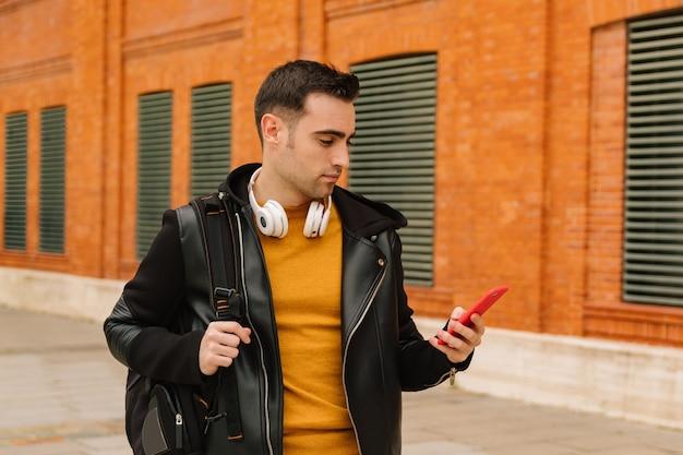 Jovem caucasiano com suéter amarelo e jaqueta de couro usando seu telefone na rua enquanto ouve música e bebe café