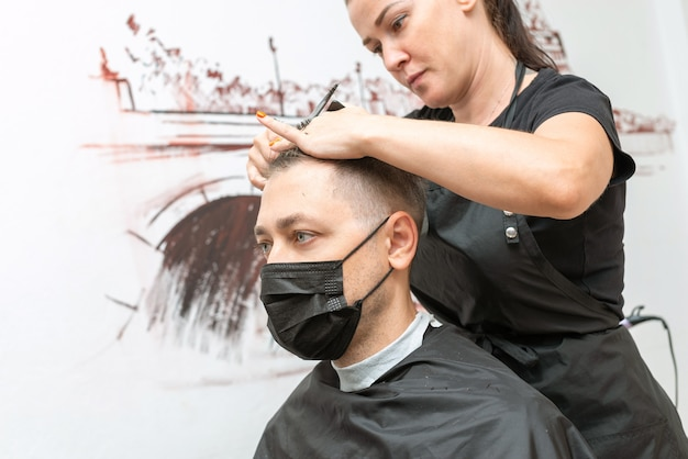 Jovem caucasiano, cortando o cabelo na barbearia usando máscara protetora. novo normal. distância social.