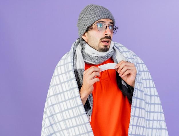 Jovem, caucasiano, doente, impressionado, usando óculos, chapéu de inverno e cachecol embrulhado em xadrez, olhando para o lado, segurando o gesso médico isolado no fundo roxo com espaço de cópia
