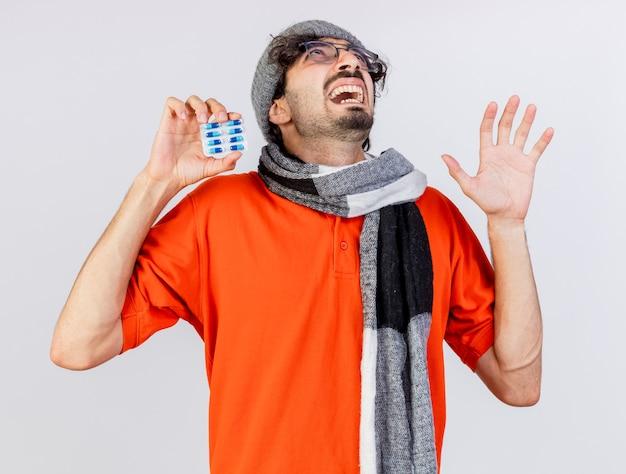 Jovem, caucasiano, doente, impressionado, usando óculos, chapéu e lenço de inverno, mostrando o pacote de cápsulas e a mão vazia olhando para cima, isolado no fundo branco