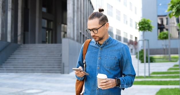 Jovem caucasiano em copos tocando e rolando no celular e segurando um café para levar na rua da cidade. homem bonito em mensagens de mensagens de texto de óculos no smartphone ao ar livre. gadget usando o conceito.