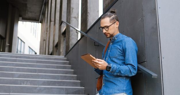 Jovem caucasiano em copos tocando e rolando no dispositivo tablet em etapas na cidade. homem bonito em mensagens de mensagens de texto de óculos e navegação online no computador gadget ao ar livre. conceito de usuário do gadget.