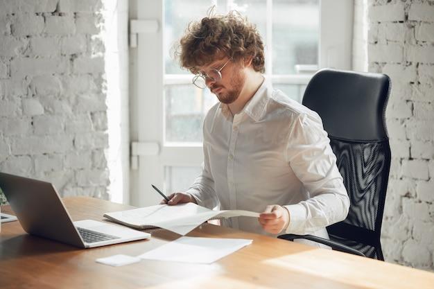 Jovem caucasiano em traje de negócios, trabalhando em um emprego de escritório online, estudando