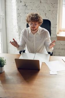Jovem caucasiano em traje de negócios, trabalhando no escritório, no emprego, estudando online