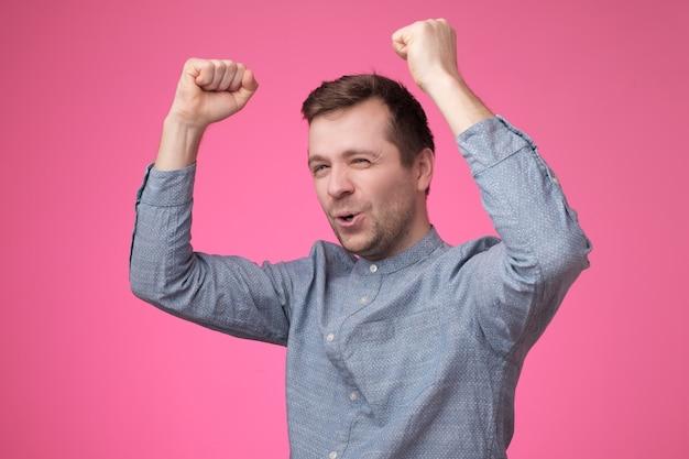 Jovem caucasiano feliz com os punhos erguidos celebrando sua vitória