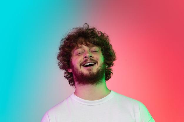 Jovem caucasiano homem retrato em fundo de estúdio gradiente em néon