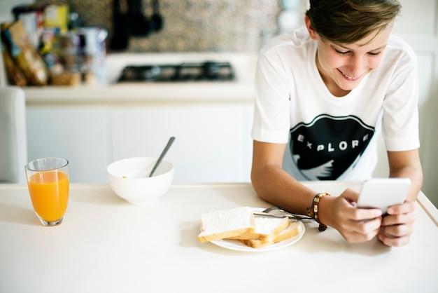 Jovem, caucasiano, homem, usando, telefone móvel, em, cozinha