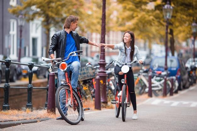 Jovem, caucasiano, par feliz, ligado, bicicletas, em, antigas, ruas, em, amsterdão