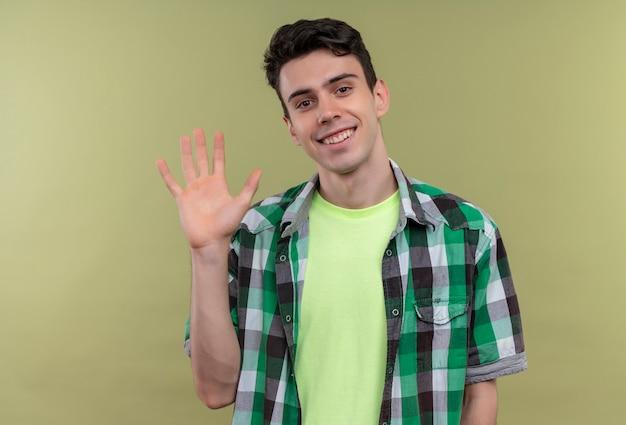 Jovem caucasiano sorridente com camisa verde e saudação em fundo verde isolado