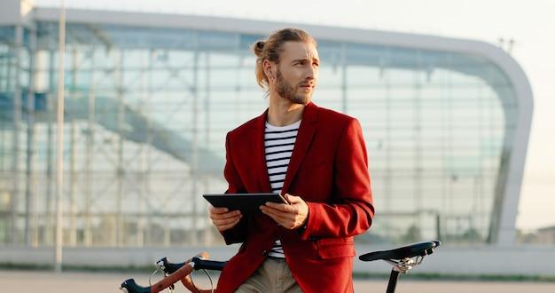Jovem caucasiano sorriu bonito homem parado na bicicleta e usando o dispositivo tablet. cara elegante de casaco vermelho apoiado na bicicleta e tocando ou rolando no computador gadget na paisagem da cidade no aeroporto.
