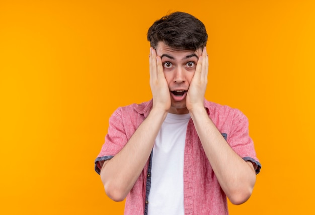 Jovem caucasiano surpreso, vestindo uma camisa rosa, colocando as mãos nas bochechas em um fundo laranja isolado