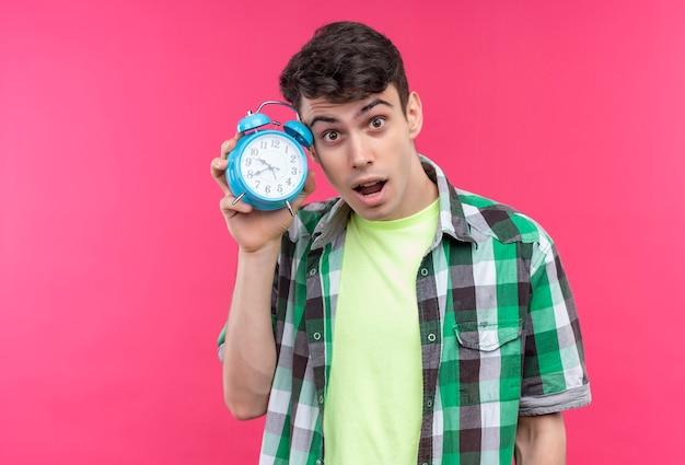 Jovem caucasiano surpreso, vestindo uma camisa verde, segurando um despertador na cabeça em um fundo rosa isolado