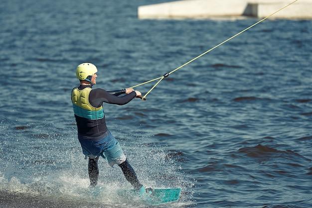 Jovem cavalgando wakeboard em um lago de verão.