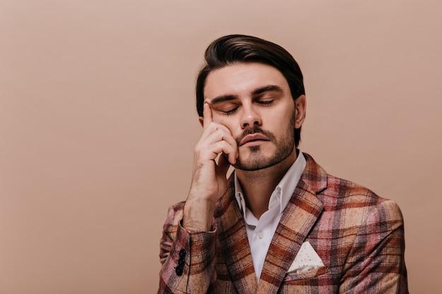 Jovem cavalheiro atraente com olhos fechados, cabelo castanho e eriçado, camisa branca e jaqueta escura quente posando contra uma parede bege e tocando o rosto com uma das mãos