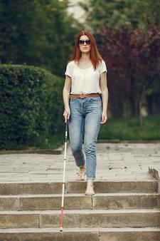 Jovem cego com longa bengala caminhando em uma cidade