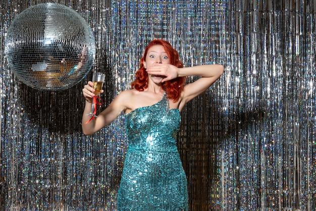 Jovem celebrando o ano novo em festa com bola de discoteca em cortinas brilhantes