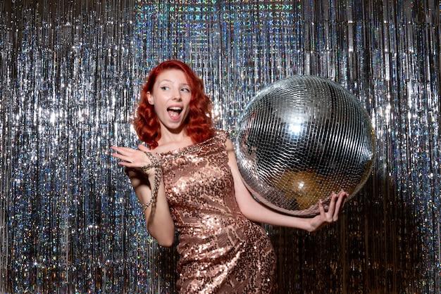 Jovem celebrando o ano novo em festa segurando uma bola de discoteca nas cortinas brilhantes