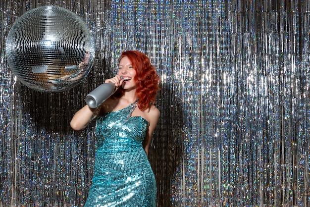 Jovem celebrando o ano novo em uma festa em cortinas brilhantes