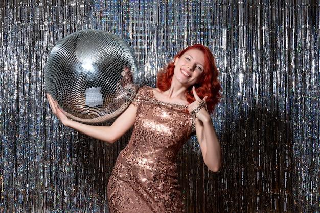 Jovem celebrando o ano novo em uma festa segurando uma bola de discoteca nas cortinas brilhantes