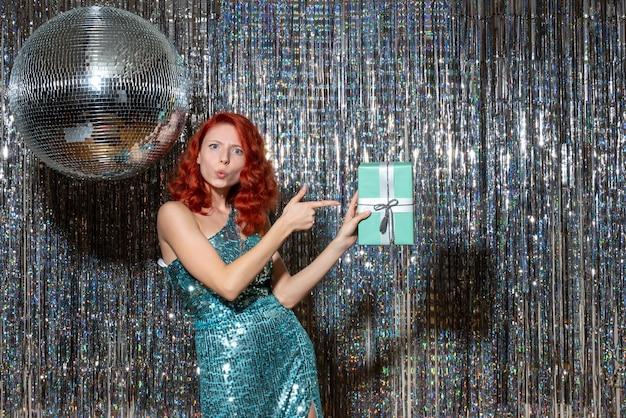 Jovem celebrando o ano novo segurando presente na festa nas cortinas brilhantes