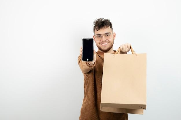 Jovem celular na mão segurando a sacola de artesanato.