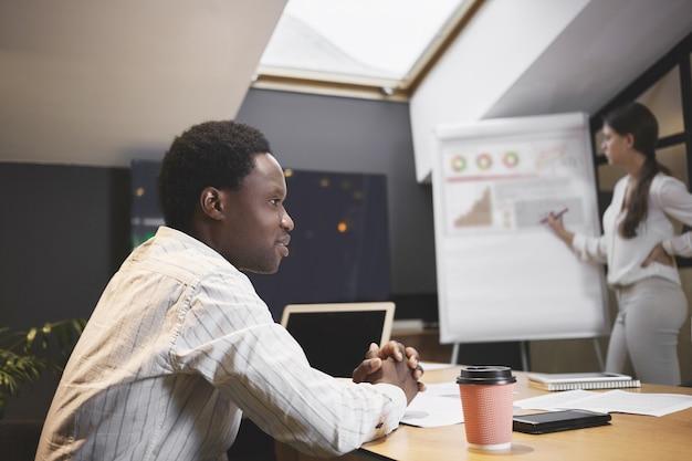 Jovem ceo africano atraente sentado na sala de conferências durante a reunião de estratégia de desenvolvimento