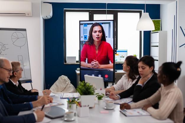 Jovem ceo falando para a câmera durante apresentação de vídeo de negócios virtuais para parceiros de negócios. empresários conversando com webcam, fazer conferência online, participar de brainstorming na internet, distância offi