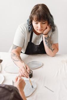 Jovem ceramista feminina trabalhando com as mãos no estúdio de cerâmica.