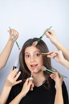 Jovem cercada pelas mãos de maquiadores com pincéis, batom e rímel perto do rosto.