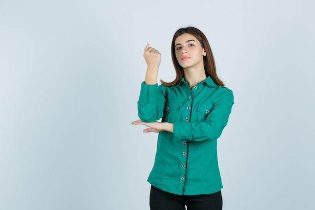 Jovem cerrando o punho na blusa verde, calça preta e parecendo confiante, vista frontal.