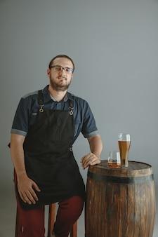 Jovem cervejeiro confiante com cerveja artesanal em vidro em um barril de madeira em cinza