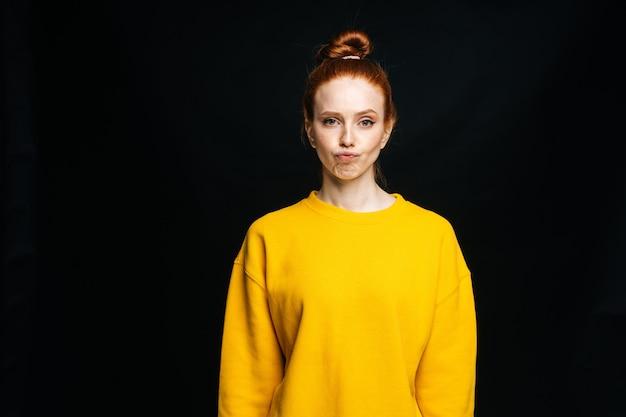 Jovem cética e descontente com um suéter amarelo posando em um fundo preto isolado