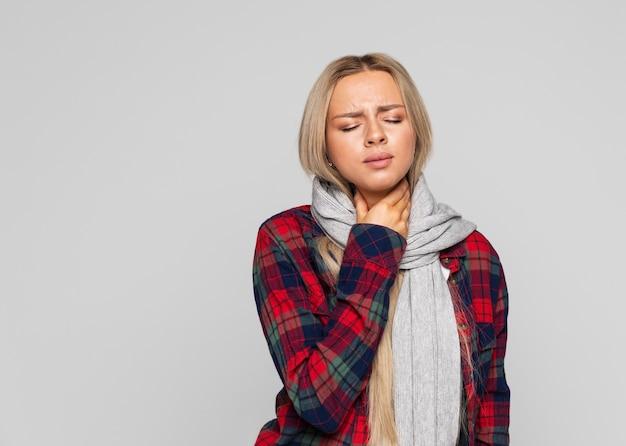 Jovem chateada de camisa quadriculada, enrolada em um lenço, com dor de garganta