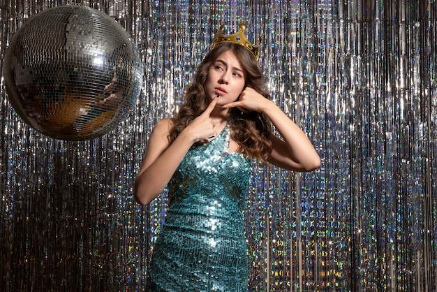 Jovem chateada e charmosa com vestido azul esverdeado brilhante com lantejoulas e coroa fazendo gesto de me ligar na festa