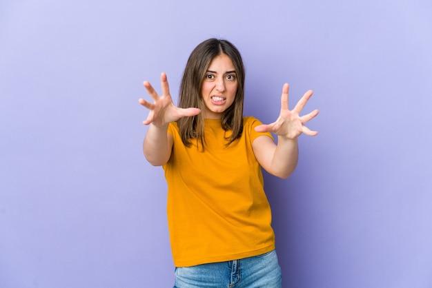 Jovem chateada gritando com as mãos tensas